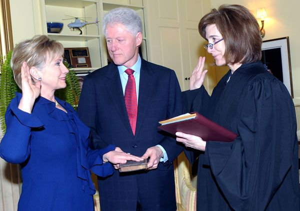 Hillary Clinton being sworn in as Secretary of State as husband and former President Bill Clinton looks on