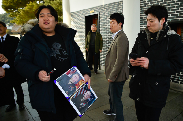 A South Korean man wearing a Mickey Mouse shirt holds photos of Secretary Mattis along with a pen, hoping to get an autograph following the wreath laying ceremony.