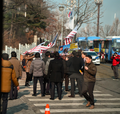 South Koreans hold American flags as they line up outside of the Seoul National Cemetery where Mattis is participating in a wreath laying ceremony.