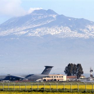 US Navy 030325 N 9693M 001 Sicilys volcano Mt. Etna is the backdrop for a U.S. Air Force C 5 and the air terminal of Naval Air Station NAS Sigonella 320x320 - Italian Government Ready To Drop U.S. Bombs On ISIS Forces In Libya From Italian Bases
