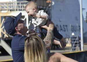 A crewmember from Coast Guard Cutter Bertholf reunites with his wife and child after the cutter returned to homeport at Coast Guard Island in Alameda, Calif., Oct. 24, 2017.