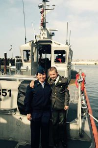 Master Chief Petty Officer Brenda Doris poses with her son on a Response Boat-Medium