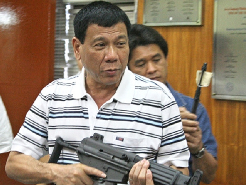 pix duterte w gun1 - Philippine president says he will eat ISIS militants' livers, lightly seasoned with salt and vinegar, for revenge